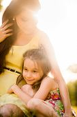 foto of cuddle  - Child is cuddling to her mother outdoor in nature at sunset - JPG
