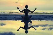 stock photo of yoga silhouette  - Silhouette of yoga woman meditating on the ocean beach - JPG