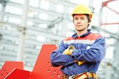 pic of millwright  - builder worker in uniform and safety protective equipment at construction site in front of metal construction frames - JPG