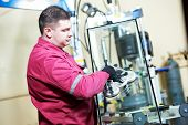 pic of suction  - glazier worker with suction cup holding glass at double glazing window manufacture - JPG