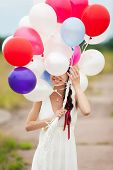 stock photo of latex woman  - Happy young woman holding in hands colorful latex balloons outdoors - JPG