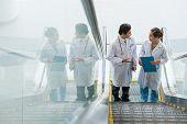 picture of escalator  - Two Asian doctors on escalator having conversation - JPG