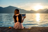 stock photo of sea-scape  - Young woman reading book and looking at beautiful sunrise on the pier with sea and mountains on background - JPG