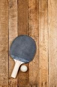 stock photo of ping pong  - Ping pong paddle and ball on vintage wooden background - JPG