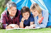 stock photo of tent  - Smiling family looking at map in tent at park - JPG