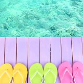 pic of beside  - Female flip flops on wooden platform beside sea - JPG