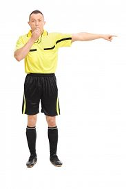 stock photo of referee  - Full length portrait of an angry football referee blowing a whistle and pointing with his hand isolated on white background - JPG