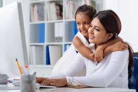 stock photo of indian  - Indian business lady working on computer while her daughter hugging her - JPG