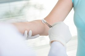 picture of disinfection  - Hands of doctor disinfecting arm before injection - JPG
