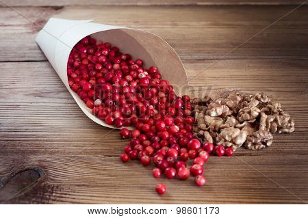 Many bright red cowberries and walnuts in a paper bag