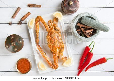 Top view cooked delicious hot and spicy sauce blue crab and ingredients, on wood background. Fresh cook with hot smoke steams.