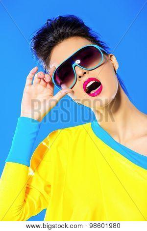 Expressive fashion model posing in vivid colourful clothes. Bright fashion. Optics, eyewear. Studio shot.