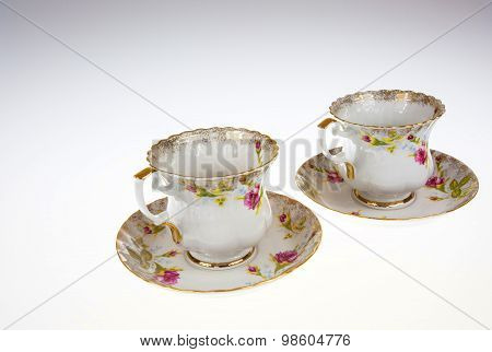 Two Porcelain, Decorative Cups With Saucers On Isolated White