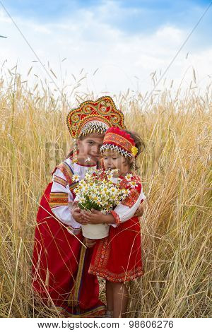 Two Girls In The Russian National Sundresses And Kokoshniks About Wheat Field With A Bouquet Of Camo