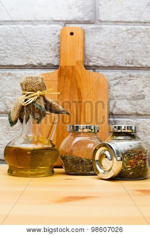 Jug Of Olive Oil, Cutting Board And Spices In The Jars