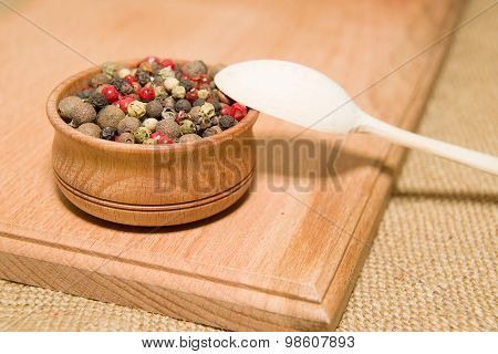 The Grains Of Pepper And Wooden Spoon On A Wooden Surface