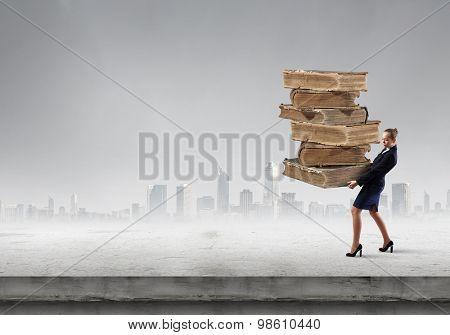 Young woman carrying huge pile of old books