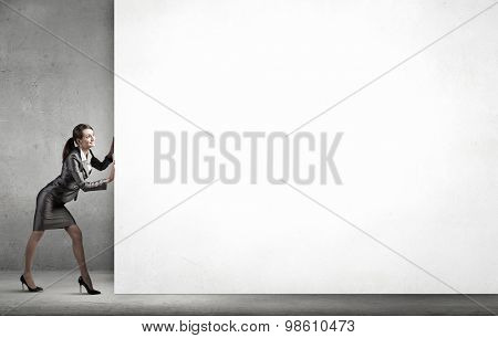 Young businesswoman making effort to move wall