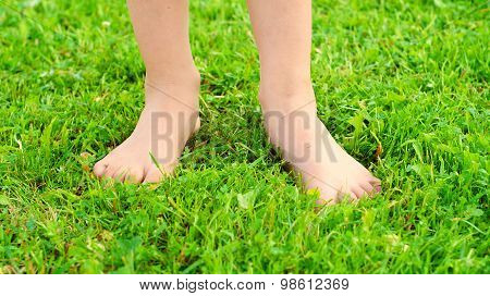 Girl's feet on the green grass