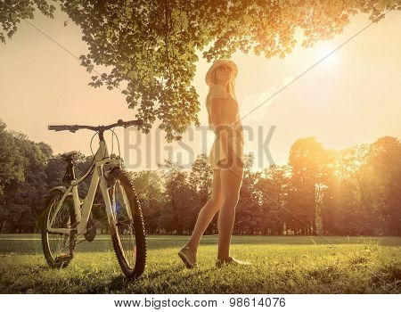Woman under sun light at day near her bicycle in the park