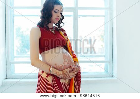 The pregnant woman belly with henna tattoo
