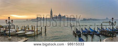 Gondolas by Saint Mark square during sunrise with San Giorgio di Maggiore church in the background in Venice Italy
