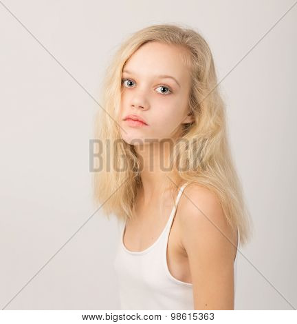 Beautiful Serious Blond Teenage Girl In White Top