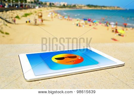a tablet computer with an icon of a sun wearing sunglasses and sweating, designed by myself, at the beach, depicting the concept of heat or heat wave