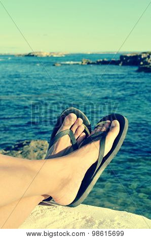 closeup of the feet of a man with flip-flops who is relaxing near the ocean in the summer, filtered