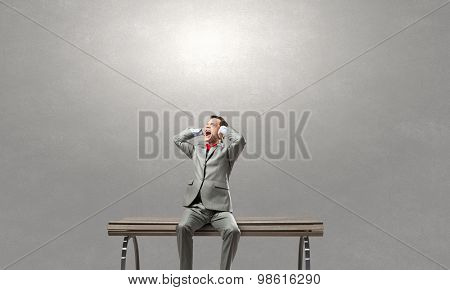 Frustrated businessman on bench closing ears with hands