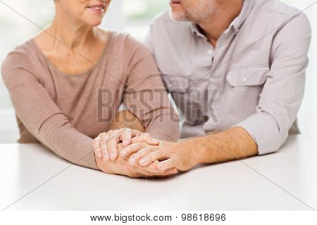 family, relations, age and people concept - close up of happy senior couple holding hands at home