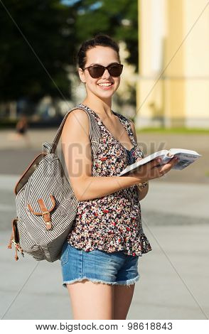 tourism, travel, summer holidays and people concept - happy teenage girl with guidebook and backpack in city