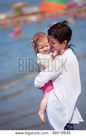 happy young mother walking on beach and push baby carriage