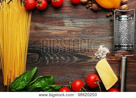 Pasta spaghetti with tomatoes, cheese and basil on rustic wooden  background