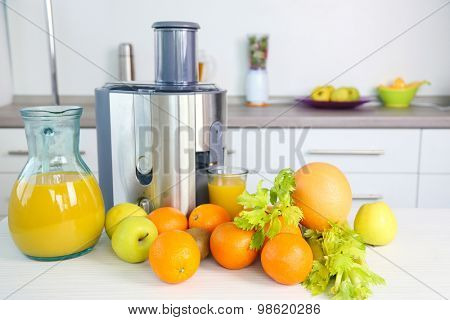 Juicer and fruits on table in kitchen, close up