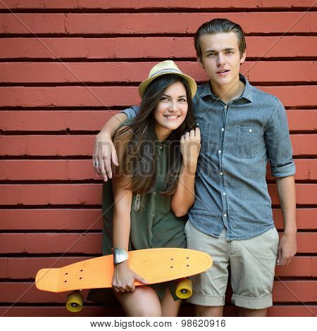 Young couple posing with penny board summer outdoor against red brick wall. Urban lifestyle, happiness, joy, friends, teenage, first love concept. Image toned and noise added.