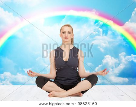 people, health, wellness and meditation concept - happy young woman meditating in yoga lotus pose on wooden floor over white clouds and rainbow on blue sky background