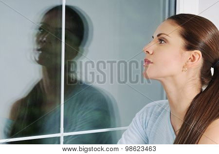 Beautiful Pensive Woman Looking Through The Window At Home