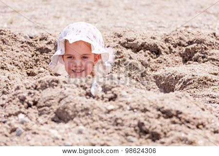 little girl playing hide and seek hidden in a hole on the beach with only her head sticking out, roo