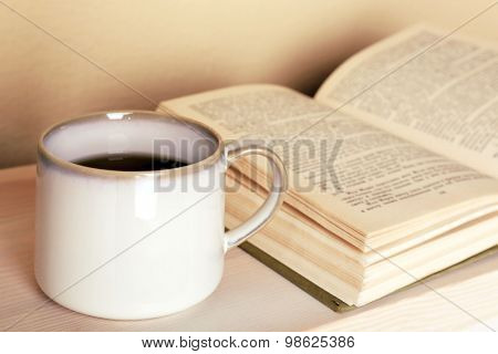 Cup of tea with book on wooden table on light wall background