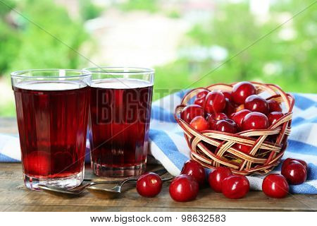 Glasses of sweet homemade cherry compote on table on bright background