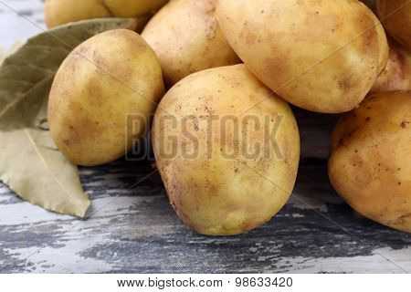 young potatoes with bay leaves on wooden table close up