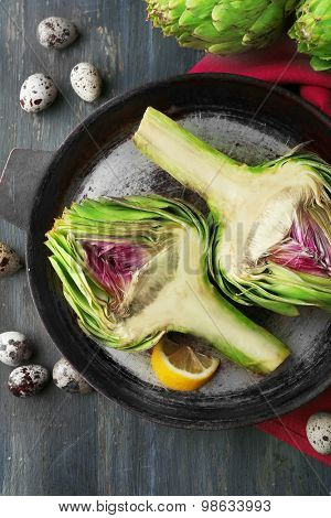 Artichokes on pan, on color wooden background