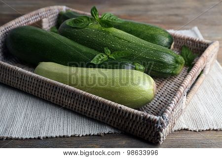 Fresh zucchini with squash and basil on wicker tray close up