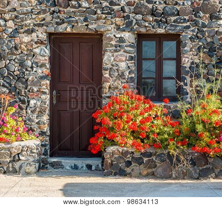 Greek Stone House With Geranium Flowers