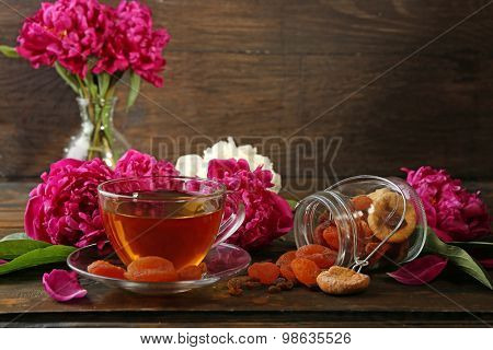 Composition with cup of herbal tea dried apricots and peony flowers on wooden background