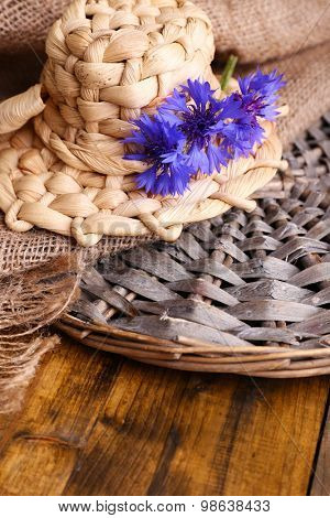 Small straw hat with cornflowers on wooden background