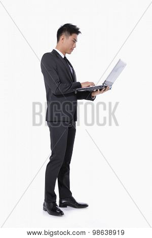Full body young business men with laptop standing in studio