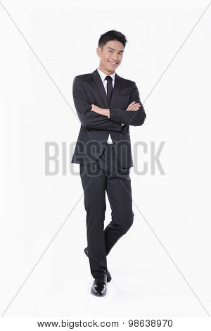 Full body young businessman with crossed arms posing in studio