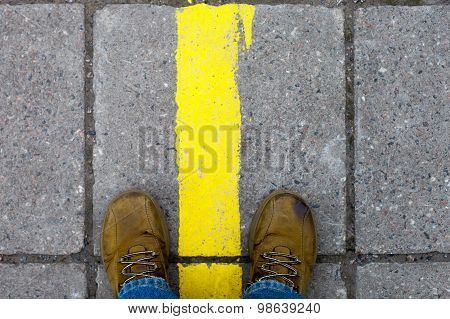Feet In The Yellow Shoes On The Pavement With Yellow Lines